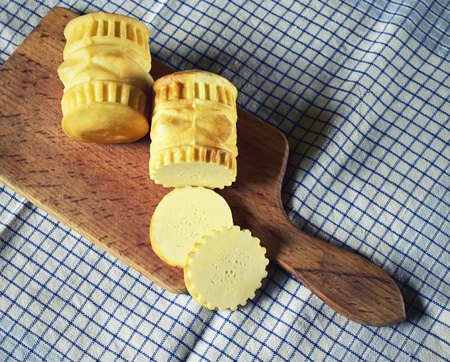 oscypek: traditional smoked cheese on a wooden plate and cloth napkin