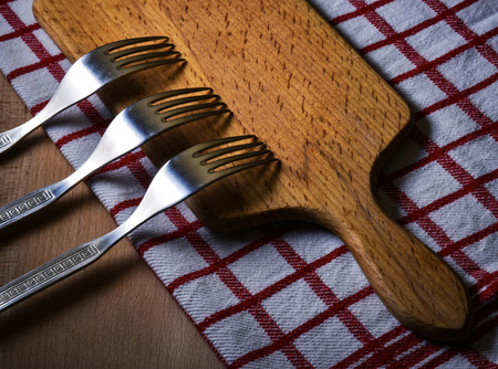 stainless: background Three forks on a wooden kitchen board Stock Photo