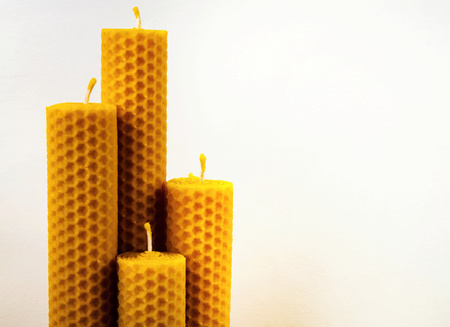 composition of four beeswax candles on a white background