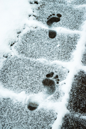 seasonal background two imprints of bare feet in the snow