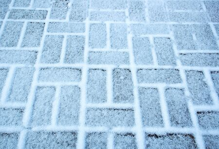 background snow cover the blocks of interlocking pavement