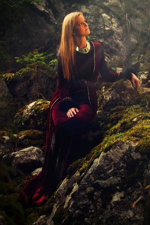 A beautiful woman fairy with long blonde hair in a historical gown is sitting amids moos covered rocks in enchanting forestral landscape photo