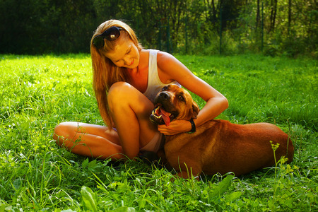 A young beautiful woman with blonde hair is playing with a mastif dog in a backyard with green grass photo