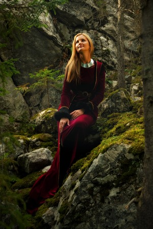 moos: A beautiful woman fairy with long blonde hair in a historical gown is sitting amids moos covered rocks in enchanting forestral landscape