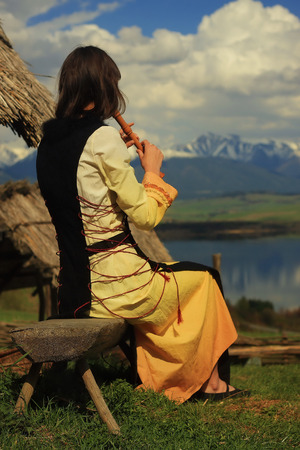 cultic: A beautiful girl in a historical costume playing her flute in an open landscape with a lake