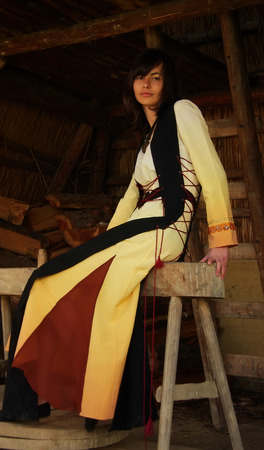 cultic: A beautiful girl in a historical costume sitting on a wooden bench inside a forest cabin