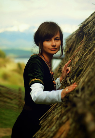 velvet dress: A beautiful young woman with dark hair, black velvet historical dress and a subtle smile is touching gently the rough surface of an ancient straw house roof