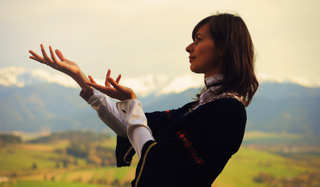 cultic: A beautiful young woman with dark hair and a historical dress posing on a meadow in open lanscape with a dramatic gesture
