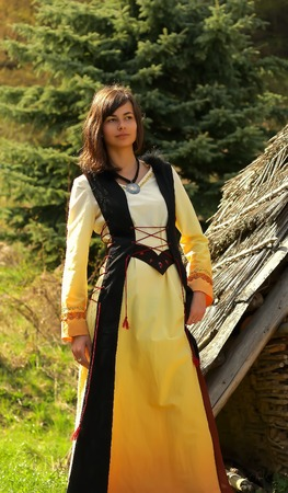 cultic: A beautiful girl in a historical costume posing in a wild landscape with a wooden log