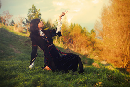 priestess: A beautiful young woman with dark hair and a historical dress posing on a meadow in open lanscape with a gesture of connection between heavenly and earth worlds