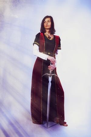 espadas medievales: Una hermosa mujer joven posando en traje hist�rico con una espada en sus manos Foto de archivo