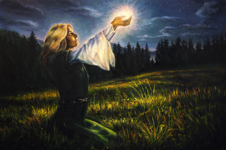enchanted: beautiful painting oil on canvas of a mystical young woman in green emerald medieval dress is holding a glowing ball of light in her palms amids a nocturnal meadow