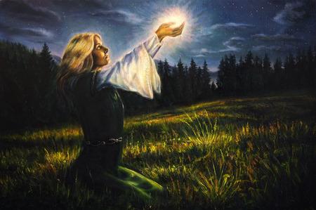 mooi schilderij olie op doek van een mystieke jonge vrouw in een groene smaragd middeleeuwse jurk houdt een gloeiende bal van licht in haar handpalmen amids een nachtelijke weide Stockfoto