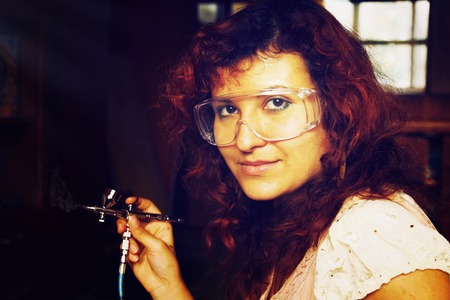 gun room: A young woman painting with airbrush equipment and airbrush gun