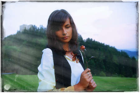 cultic: beautiful girl in historical costume in a wild meadow landscape holding a secretful  romantic rose in her hands