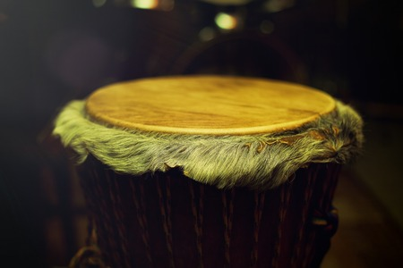 new age music: Original african djembe drum with leather lamina with beautiful hair in beautiful tyellow light with dark background Stock Photo