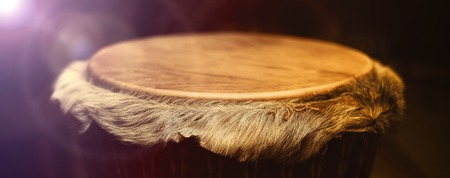 new age music: Original african djembe drum with leather lamina with beautiful hair in beautiful effect violet yellow light with dark background