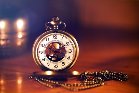 pocketwatch: retro gold pocket watch in beautiful light candle on brown background