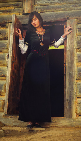 log hair: A beautiful young woman with dark hair in a black velvet historical dress is standing at the door of a forest log cottage