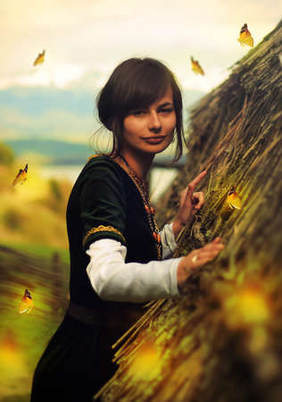 cultic: A beautiful young woman with dark hair, black velvet historical dress and a subtle smile is touching gently the rough surface of an ancient straw house roof