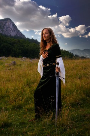 enchanting: A young beautiful woman with blonde hair in historical dress is posing in an enchanting open landscape with trees and a mountain meadow, with a hand-to-heart gesture and mystical medieval sword.