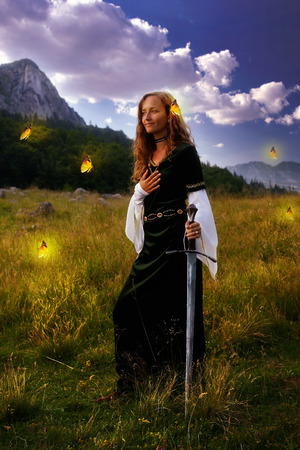 medievales: Una mujer hermosa joven con el pelo rubio en traje hist�rico est� planteando en un paisaje abierto encantador con �rboles y un prado de la monta�a, con un gesto de mano a coraz�n y espada medieval m�stica. con mariposas amarillas