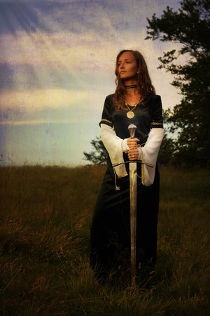 A young beautiful woman with blonde hair in black velvet medieval dress is standing alone on a wild meadow in a mystical midsummer evening light, holding a sword in her hands