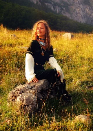 velvet dress: young beautiful woman with long blonde hair in black velvet medieval dress is sitting alone on a rock on a wild mountain meadow, looking up, with her face gently enlighted
