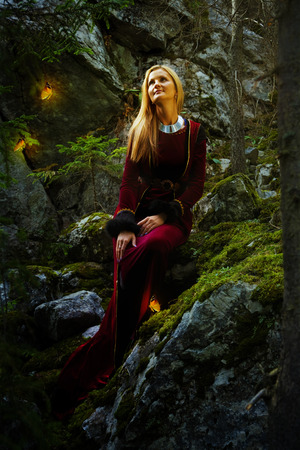 velvet dress: beautiful woman fairy with long blonde hair in a historical gown is turning her head just to have a glimpse of shining golden butterflies flying around her in the deep woods