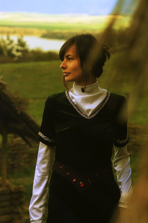 cultic: A beautiful young woman with dark hair and a black velvet historical dress walking through an open landscape with a lake