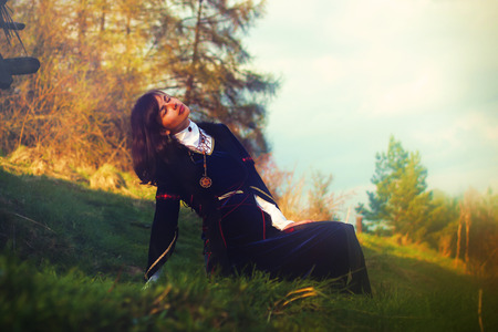 cultic: A beautiful young woman with dark hair and a historical dress posing on a meadow in open lanscape