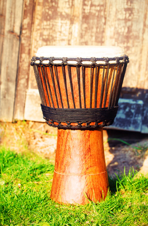 new age music: Original african djembe drum with leather lamina, on green in sun light.