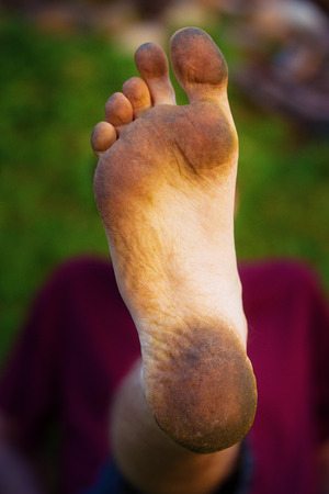 dirty foot man on green background photo