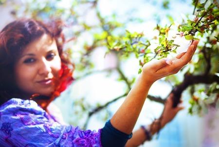 poetic: Young poetic woman with magnolia tree in the spring time. Woman holding flower