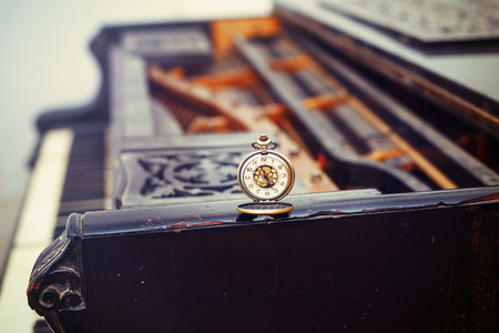 Vintage piano keys with antique pocket watch – time concept. photo