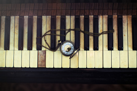 Vintage piano keys with antique pocket watch with a chain – time concept photo
