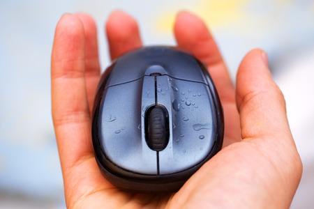 clicked: Open Hand and computer mouse  with water drops. Stock Photo