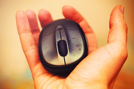 clicked: Open Hand and computer mouse  with water drops. Vintage picture