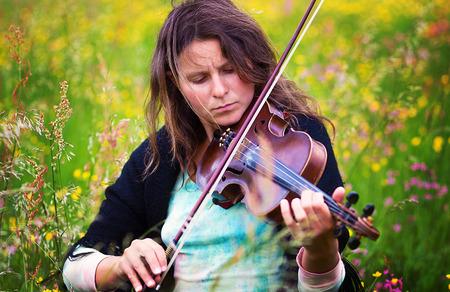 violinista: violinista en un prado lleno de flores. Foto de archivo
