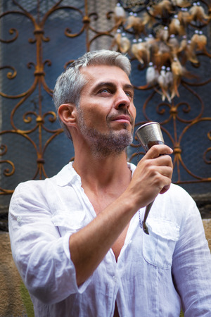 Sexi Man in a white shirt and medieval mead horn in hand. Toast concept. Ornamental window on background, and Dream Catcher. in sun light Stock Photo