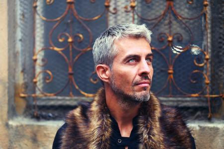 animal eye: Portrait of a sexy man in wolf  fur and ornamental medieval window on background.