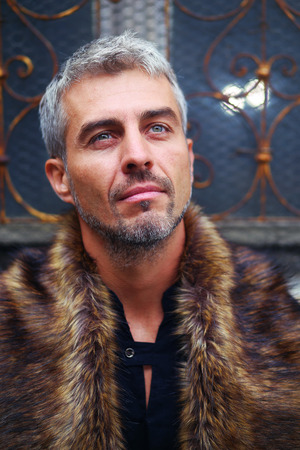 sexy fur: Portrait of a sexy man in wolf  fur and ornamental medieval window on background.