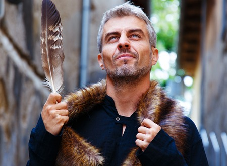 disgruntled: Portrait of a sexy man and wolf furry and eagle feathers, a disgruntled expression on his face