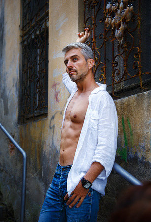 muscular body: fashion portrait hot male model in stylish jeans and shirt with muscular body posing. And Dream Catcher. Stock Photo