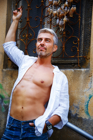 clothing model: Man in a white shirt and ornamental window on background.