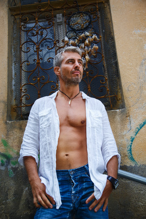 muscular body: fashion portrait hot male model in stylish jeans and shirt with muscular body posing.