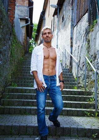 shirtless: retrato de la moda modelo masculino caliente en pantalones vaqueros con estilo y camisa con posando cuerpo musculoso.