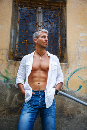 muscle guy: fashion portrait hot male model in stylish jeans and shirt with muscular body posing.