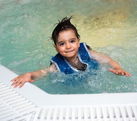 unkempt: Young boy with inflatable swimming vest in the pool, has a happy smile.  Eye contact.