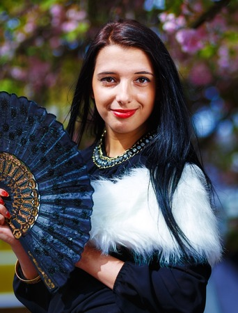 white fur: Beautiful Girl with flowers and glamour white fur and black fan